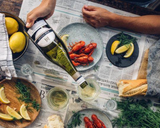Mud House Sauvignon Blanc -viiniä kaadetaan lasiin rapupöydässä.